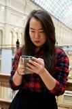 Девушка смотря телефон Стоковая Фотография