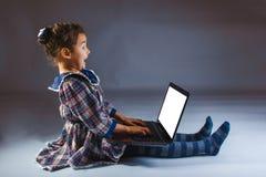 Девушка смотря удивленный компьютер Стоковые Изображения