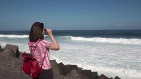 Девушка смотря через бинокли на океане видеоматериал