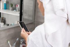 Девушка смотря smartphone в ванной комнате Стоковые Изображения RF