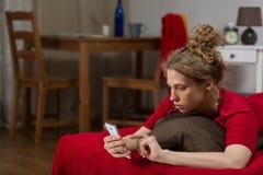 Девушка смотря smartphone Стоковые Фото
