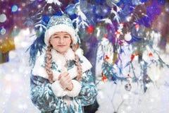 Девушка снега в портрете леса маленькой девочки в зиме в элегантном праздничном костюме ребенок греет его руки Счастливое новое…  стоковые изображения