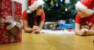 Девушка снега с гномом лежа около праздничной рождественской елки говоря друг к другу акции видеоматериалы
