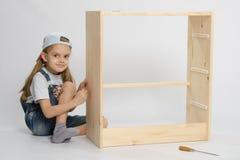 Девушка собирает комод мебели отброса ящиков Стоковая Фотография