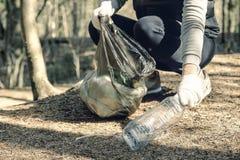 Девушка собирает пластиковое Кладет его в сумку отброса Проблема загрязнения окружающей среды от пластикового отхода Экологическо стоковая фотография rf