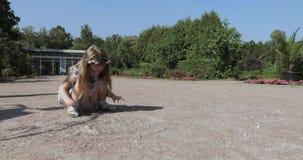 Девушка собирает утесы и песок акции видеоматериалы