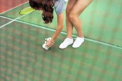 Девушка собирая шарик бадминтона сеть стоковая фотография rf