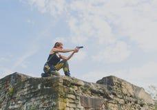 Девушка солдат при красные волосы держа пистолет против неба Стоковые Изображения RF