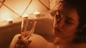 Девушка со стеклом шампанского алкогольного напитка релаксация и отдых в жемчужной ванне акции видеоматериалы