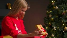 Девушка со шляпой рождества делает желания и раскрывает пакет подарка рождества Концепция праздников и Нового Года Девушка видеоматериал