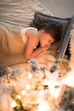 Девушка спать под рождественской елкой, гирлянда, света, Christm Стоковое Изображение RF
