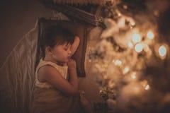 Девушка спать под рождественской елкой, гирлянда, света, Christm Стоковые Фото