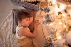 Девушка спать под рождественской елкой, гирлянда, света, Christm Стоковое фото RF