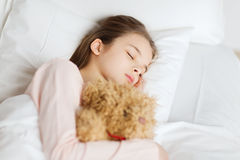 Девушка спать с игрушкой плюшевого медвежонка в кровати дома Стоковое фото RF