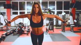 Девушка спортсмена в sportswear разрабатывая и тренируя ее оружия и плеча в спортзале акции видеоматериалы