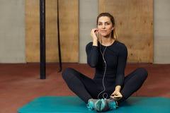 Девушка спортсмена отдыхая с наушниками и mp3 плэйер Стоковое Изображение RF