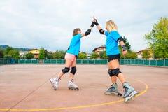 Девушка 2 спорт в Rollerblade тенниса дает вам хлоп их рука стоковые фотографии rf