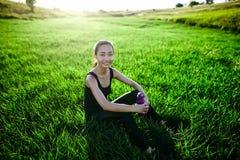 Девушка спорт ослабляет на траве при бутылка смотря в камеру Стоковые Фото