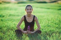 Девушка спорт ослабляет на траве при бутылка смотря в камеру Стоковая Фотография RF