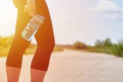 Девушка спорт стоит на дороге с бутылкой с водой спорт в ее руке Резвит образ жизни, здоровье стоковые изображения