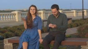 Девушка спрашивает, что человек останавливает использовать сотовый телефон стоковые изображения rf