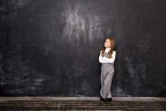 Девушка стоит задумчиво на доске Предпосылка с свободным местом на левой стороне стоковые изображения