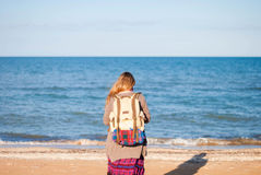 Девушка стоит назад и смотрит море Девушка Hippie смотрит море Женщина с бутылкой вина морем hippie Стоковое Изображение RF