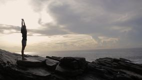 Девушка стоит на утесах около океана сток-видео