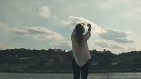 Девушка стоит около реки и joyfully подъемов сток-видео