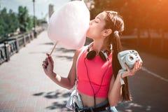 Девушка стоящие внешние и еда конфета хлопка Она держит аудиоплейер в другой руке Наушники Стоковые Фотографии RF