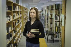 Девушка стоя в библиотеке с книгами в ее руках стоковое изображение rf