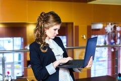 Девушка стоя в кафе и работая на компьтер-книжке Стоковое фото RF