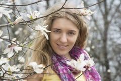 Девушка стоя в цветках магнолии Стоковое Фото