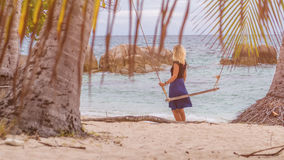 Девушка стоя за качанием на тропическом пляже на вечере стоковое фото