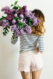 Девушка стоя назад с букетом сирени на белой предпосылке стоковая фотография
