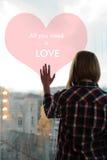 Девушка стоя назад на балконе с рукой на стекле Стоковая Фотография RF