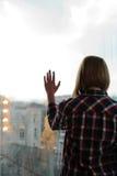 Девушка стоя назад на балконе с рукой на стекле Стоковая Фотография