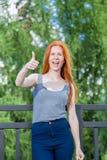Девушка стоя на балконе гостиницы, усмехаясь и держа большой палец руки вверх Стоковые Фото