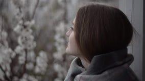 Девушка стоя на балконе окном на предпосылке blossoming абрикосов сток-видео
