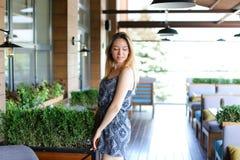 Девушка стоя на кафе около зеленых palnts Стоковые Фото