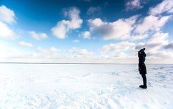 Девушка стоя на крае замороженного моря смотря прочь Стоковые Изображения