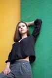 Девушка стоя на красочных стенах Стоковые Фото