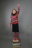 Девушка стоя на куче книг стоковая фотография rf