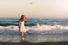 Девушка стоя на пляже Стоковые Фото