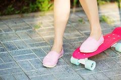 Девушка стоя на розовом скейтборде outdoors Изображение крупного плана fe Стоковое Изображение RF