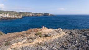 Девушка стоя на скале и смотря море bali Индонесия стоковая фотография rf