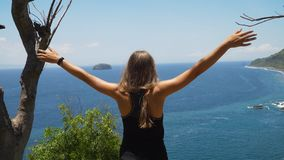 Девушка стоя на скале и смотря море bali Индонесия стоковое фото
