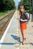 Девушка стоя на станции ждать на поезде Стоковые Изображения RF