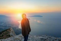 Девушка стоя на утесе в лучах восходящего солнца, путешествии стоковое фото rf