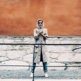 Девушка стоя на улице города в яркой стене Стоковое Изображение